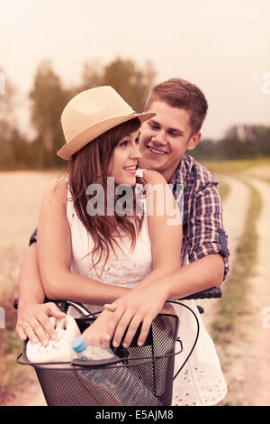 Young couple having fun on bicycle, Debica, Poland - Stock Photo