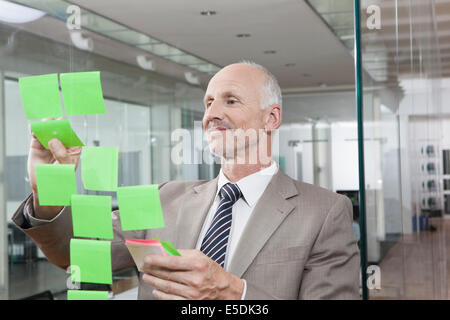 Germany, Munich, Businessman in office, putting sticky notes on glass pane - Stockfoto