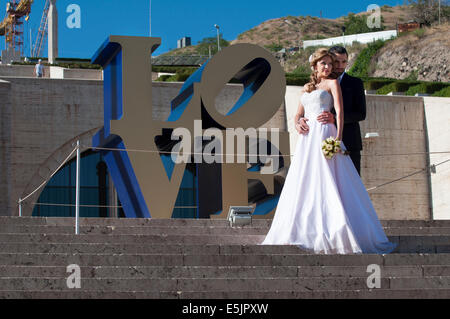 A couple in wedding clothes in front of Love statue by Robert Indiana, Cascade of Yerevan, Armenia - Stockfoto