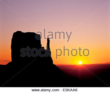 Sunrise behind the west mitten butte in Monument Valley, a Navajo Tribal Park on the Navajo reservation in Arizona - Stock Photo