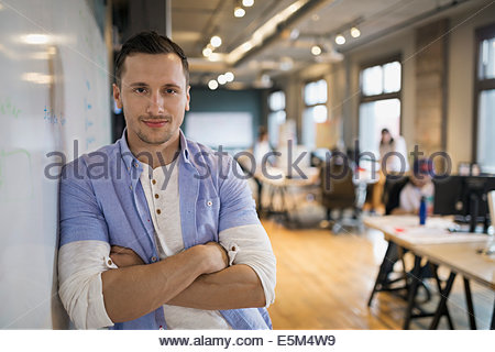 Portrait of confident businessman leaning on whiteboard - Stock Photo