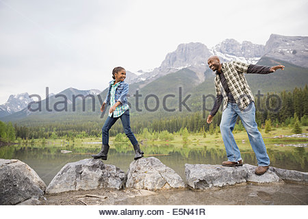 Father and daughter balancing on rocks at lake - Stock Photo