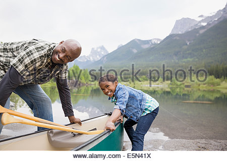 Father and daughter pulling canoe into lake - Stock Photo