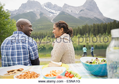 Couple sitting at picnic table near lake - Stock Photo