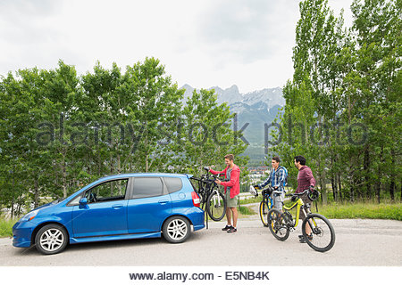 Men removing bicycles from bike rack on car - Stock Photo