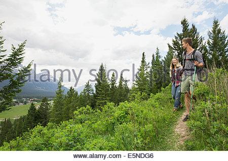 Couple hiking on trail near mountains - Stock Photo