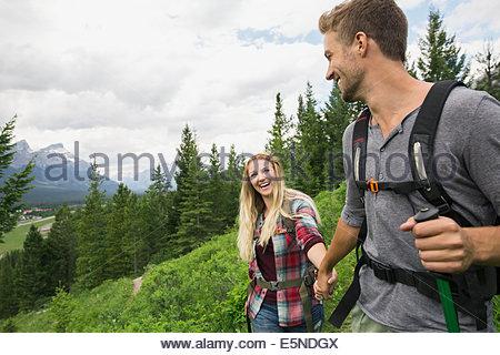 Smiling couple hiking near mountains - Stock Photo