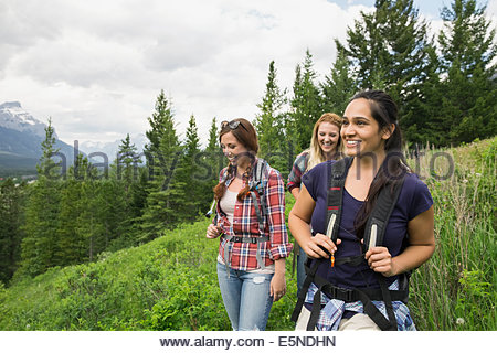 Friends hiking on trail near mountains - Stock Photo