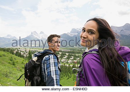 Couple with backpacks hiking near mountains - Stockfoto