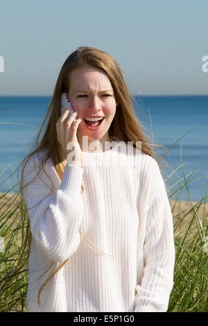 17 year old Caucasian girl at shore, talking on mobile phone - Stock Photo