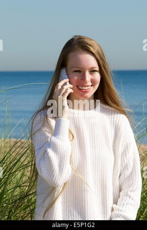 17 year old Caucasian girl at shore, talking on mobile phone. - Stock Photo