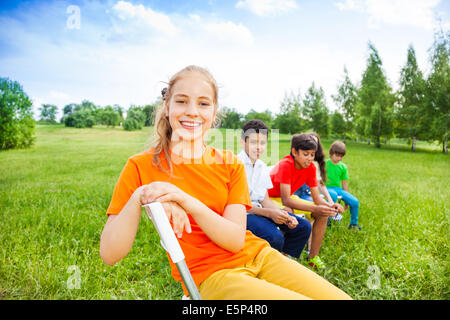 Five happy kids sit on chairs in row outdoors - Stock Photo