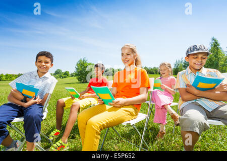 Happy kids hold exercise books and sit on chairs - Stock Photo