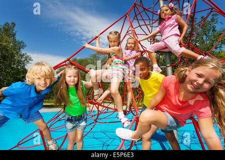 Happy group of kids on red ropes together in park - Stock Photo