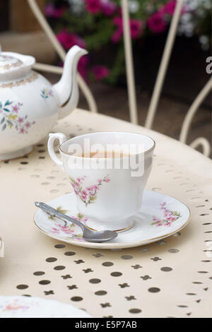 Afternoon tea served in vintage floral mismatched cups and saucers - Stockfoto
