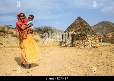 Mother with her son in front of a traditional hut in the highlands of Eritrea, Africa - Stock Photo