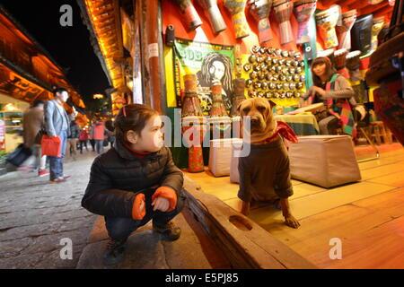 Young girl sitting next to a dog that is wearing bandana and sweater, Lijiang, Yunnan, China, Asia - Stock Photo