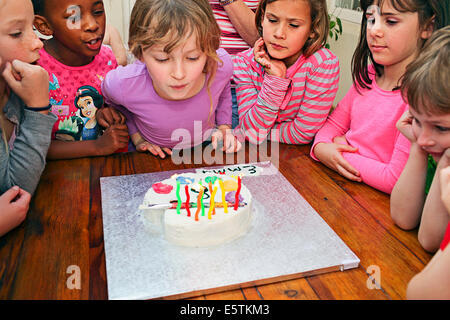 Three Years Old Girl Blowing Candles On Birthday Cake