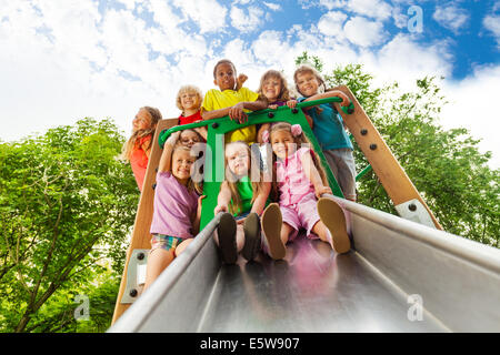 View from below of many kids on playground chute - Stock Photo