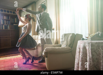 Young vintage couple dancing rock n roll in sitting room - Stock Photo