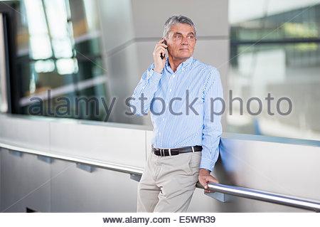 Senior adult businessman using mobile phone - Stock Photo