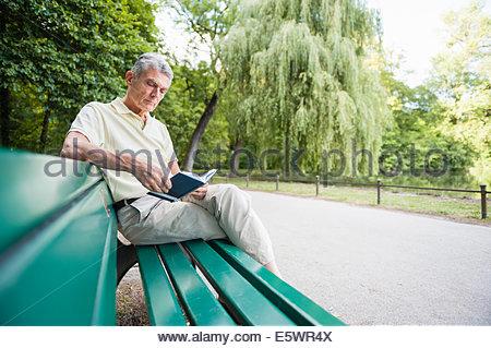 Senior adult man sitting on bench reading book - Stock Photo