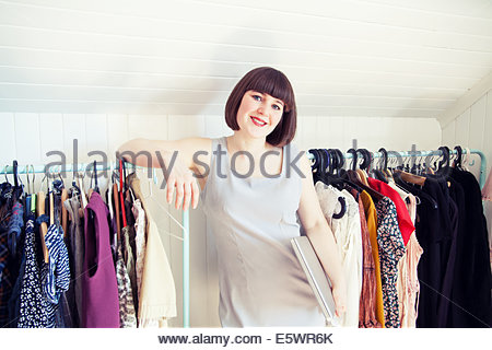 Portrait of young woman leaning on clothes rail in dressing room - Stock Photo