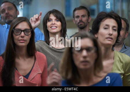Group watching presentation, woman raising hand - Stock Photo