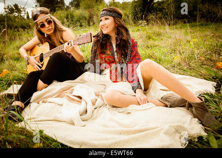 Hippy girls on blanket in field, playing guitar - Stock Photo