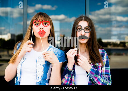 Portrait of two young women holding up lip and eye costume masks - Stock Photo