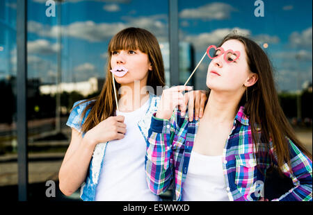 Two young women looking up with lip and spectacles costume masks - Stock Photo