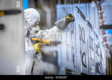 Worker powder coating parts in paint spray booth in sheet metal factory - Stockfoto