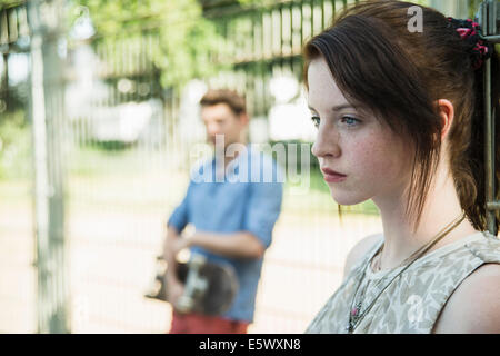 Young couple keeping distance in park after argument - Stock Photo
