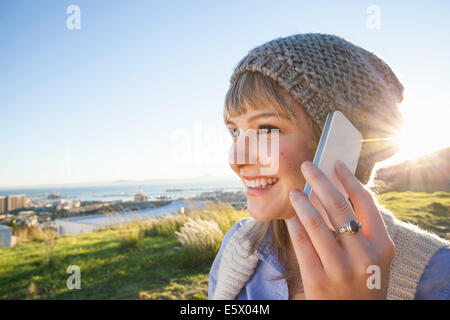Young woman chatting on smartphone, view of harbour in background, Cape Town, South Africa - Stock Photo