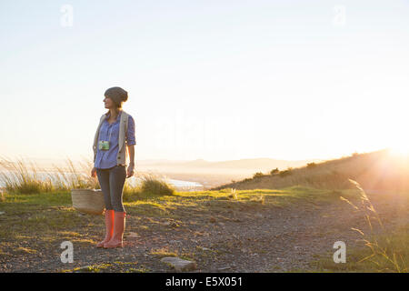 Young woman standing on hill at sunset - Stock Photo