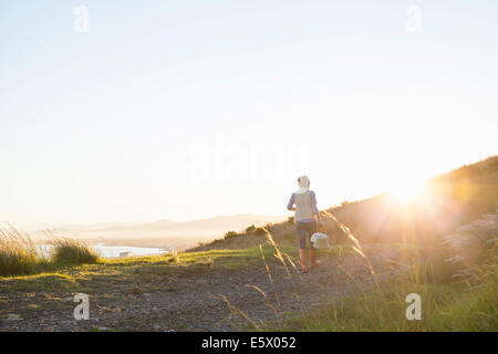 Young woman walking on hill at sunset - Stock Photo