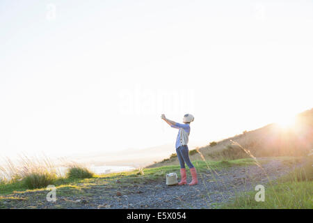 Young woman taking photograph on hill at sunset - Stock Photo