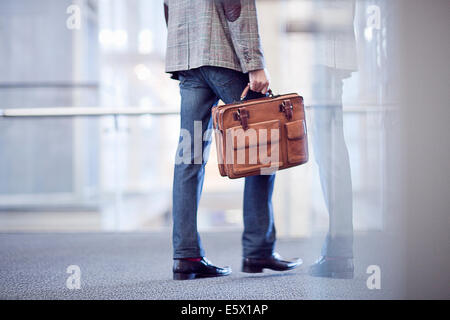 Cropped shot of young businessman with briefcase in conference centre - Stock Photo