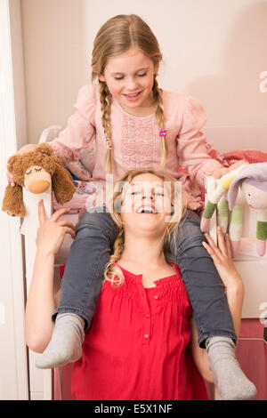 Girl laughing whilst giving sister a shoulder ride in bedroom - Stock Photo