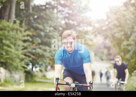 Cyclists riding on leafy countryside road, Cotswolds, UK - Stock Photo
