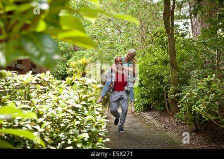 Happy couple having fun giving piggy back in garden - Stock Photo