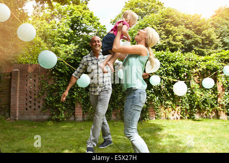 Happy couple playing with toddler daughter in garden - Stock Photo