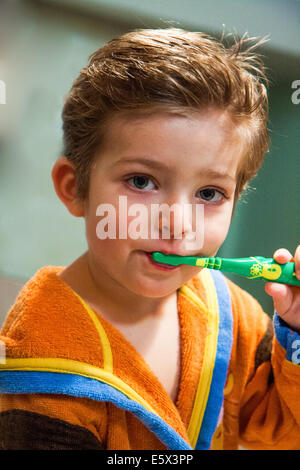 Child brushes his teeth with a bathrobe - Stock Photo
