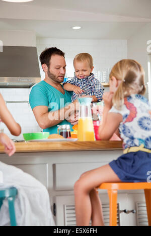 Father multi tasking breakfast with son and daughters - Stock Photo