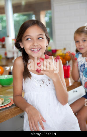Two mischievous sisters with raspberries on their fingers in kitchen - Stock Photo