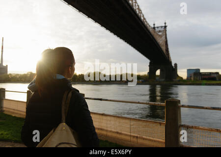 Young female runner gazing out on waterfront, Roosevelt Island, New York City, USA - Stock Photo