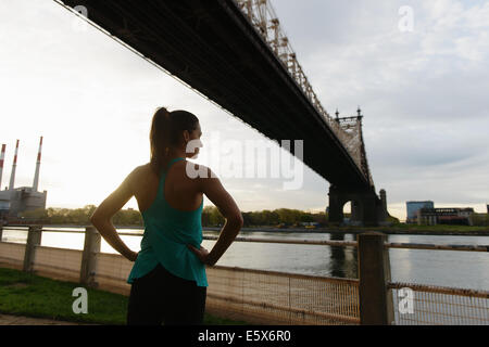Young female runner with hands on hips on waterfront, Roosevelt Island, New York City, USA - Stock Photo