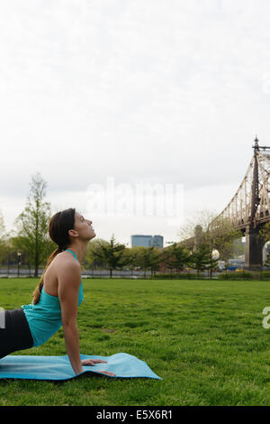 Young woman practicing yoga in city park - Stock Photo