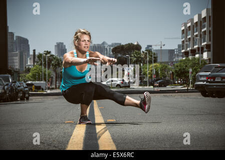 Young adult woman balancing on one foot in road - Stock Photo