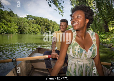 Young couple in rowing boat on lake in Central Park, New York City, USA - Stock Photo